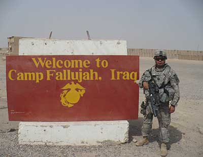 Manuel Cano standing next to Camp Fallujah Welcome Sign